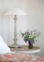 Detail of a vase of delicate purple flowers placed on a mosaic bedside table