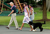 Washington, DC - June 25, 2009 -- United States Vice President Joseph Biden, first lady Michelle Obama, Malia Obama and family dog Bo arrive at a luau for members of Congress and their families on the South Lawn of the White House June 25, 2009 in Washington, DC. In a celebration of the president's home state, the South Lawn was decorated with tiki torches and palm huts and the meal prepared by famous Hawaiian chef Alan Wong. .Credit: Chip Somodevilla - Pool via CNP