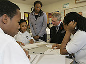 Washington, D.C. - November 2, 2005 -- Prince Charles sits with SEED School students, from left, Percy Thomas, 14, Tysheen Murray, 12, and Chrystal Germany, 14, right, and their teacher Melanie Brown, standing center, during a visit to the school in Washington, Wednesday, Nov. 2, 2005. The SEED School offers an intensive academic and boarding education to 320 urban children in grades seven through twelve. Prince Charles and Camilla are on an 8-day tour of the United States. .Credit: AP Photo/Susan Walsh via CNP.(Restriction: No New York Metro or other Newspapers within a 75 mile radius of New York City)