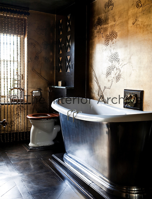 The bathroom has been papered with an Oriental-style gold paper decorated with birds and flowers