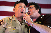 Kicking off the United Services Organization (USO) show, General Tommy Franks, Commander, United States Forces Central Command (CENTCOM) sings a duet with Wayne Newton aboard USS Nimitz (CVN 68) on June 19, 2003.  Nimitz Carrier Strike Force and Carrier Air Wing Eleven (CVW-11) are deployed in support of Operation Iraqi Freedom.  Operation Iraqi Freedom is the multi-national coalition effort to liberate the Iraqi people, eliminate Iraq's weapons of mass destruction, and end the regime of Saddam Hussein. .Credit: U.S. Navy via CNP