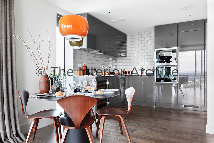 An orange retro style pendant light hanging above a round dining table with Norman Cherner chairs in an open plan kitchen with glossy grey units.
