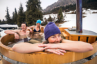 Ski tourers sit in a hot tub at their yurt camp in Kyrgyzstan