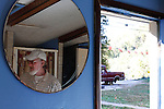 "Leamon Maggard, 71, lives alone in a small apartment on the side of  highway 421.  The apartment has one room that serves as his kitchen, living room and bedroom as well as one bathroom.  On his bedside table Maggard has a frame holding a number of pictures of his relatives.  He also has a frame holding several pictures of his brother, who died ""a long, long time ago.""  Maggard's son Otis Coots lives in a neighboring apartment and says Maggard has fairly severe Alzheimer's.  Photo by Morgan Eads"