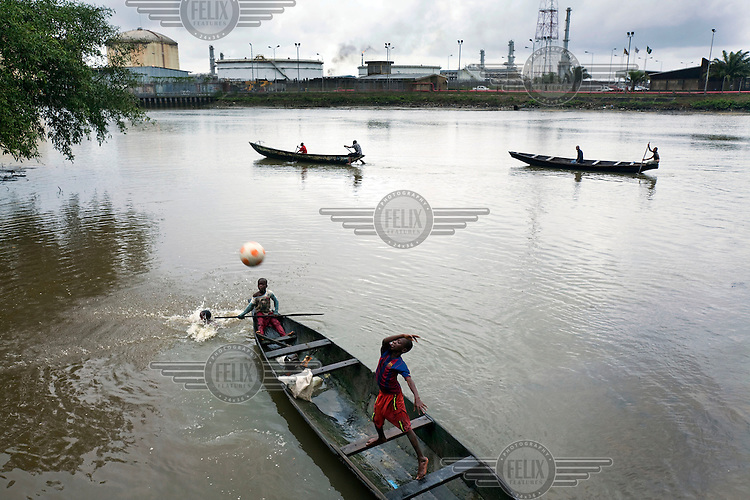 Children play with a ball in a boat as fisherman catch fish of Bonny Island with a gas flare in the background. Oil pollution in the Delta is causing tremendous problems for the local community.