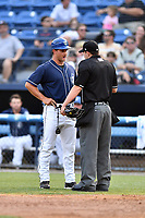 Asheville Tourists manager Warren Schaeffer (13) discusses the strike zone with home plate umpire Forrest Ladd during a game against the Charleston RiverDogs at McCormick Field on July 6, 2017 in Asheville, North Carolina. The Tourists defeated the RiverDogs 13-9. (Tony Farlow/Four Seam Images)