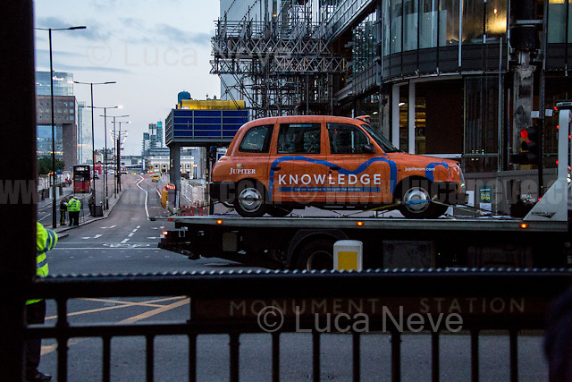 Taxis &amp; other vehicles left on London Bridge are loaded on tracks and taken away.<br />