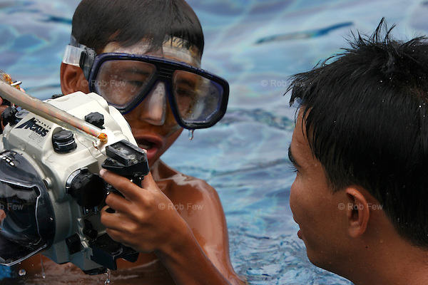 But change is possible. Here, a Moken boy enthusiastically learns to take pictures underwater with one of the InSIGHT Out! trainers.<br /> <br /> The InSIGHT Out! project provides photography and creative writing training to marginalised children in southern Thailand. It is run by the NGO Grassroots for Human Rights Education and Development (GHRE), along with volounteer teachers from Bangkok University and the professional photographic community.