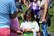 Bethesda, MD - June 25, 2016: 7-year-old Maxi Evans of Gaithersburg, MD, marvels at a golf ball given to her by Jim Furyk's caddy Michael Cowen, during Round 3 of professional play at the Quicken Loans National Tournament at the Congressional Country Club in Bethesda, MD, June 25, 2016.  (Photo by Don Baxter/Media Images International)