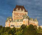 View of the Château Frontenac hotel from the St. Lawrence River waterfront at sunrise.