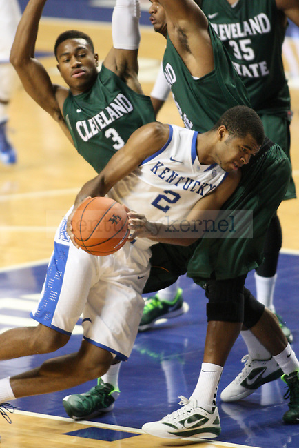 UK guard Aaron Harrison drives the ball forward against Cleveland State guard Trey Lewis and forward Anton Grady during the second half of the University of Kentucky men's basketball game vs. Cleveland State at Rupp Arena in Lexington, Ky., on Monday, November 25, 2013. UK won 68-61. Photo by Tessa Lighty | Staff