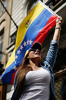 A woman holds up a flag while Venezuela's government opposition members take part in a rally against president Maduro and his government in front of Venezuela's consulate in New York,  04/19/2015. Eduardo MunozAlvarez/VIEWpress