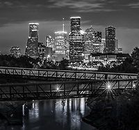 We captured a black and white vertical pano of Rosemont pedestrian bridge and the Houston skyline over the Buffalo Bayou at night in downtown area of the city. Houston has a lot to offer with many parks, cultural events in the theater district, along with many sport and music event to name yet a few things to do. Houston also has a reputation of a place to see top notched performing art along with access to several museums in the area. The Theater distric performing art has nine major performing art group along with six performance halls. You can see Opera, a plays, the ballet and any number of music events including the well known Houston Symphony Orchestra Houston has some top notch restaurants and places to stay. Houston has a population of around 3.4 million people it the largest city in Texas and the fourth largest in the nation. The skyline of Houston is a very impressive site with some of the tallest modern skyscrapers buildings in the US. In this image you can see the Heritage Plaza, Chevron, Wells Fargo and the tallest building in Houston the J P Morgan Chase Tower at 1002 ft and it is the 17 tallest in the US. Houston is the seat of Harris county and was founded in 1837 near the banks of the Buffalo Bayou or Allen Landing as it is called today. Houston skyline stock.