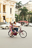 VIETNAM, Hanoi, three young girls ride through the center of town