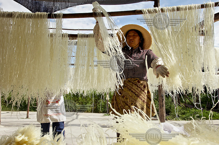 A woman dries rice noodles in the sun. /Felix Features