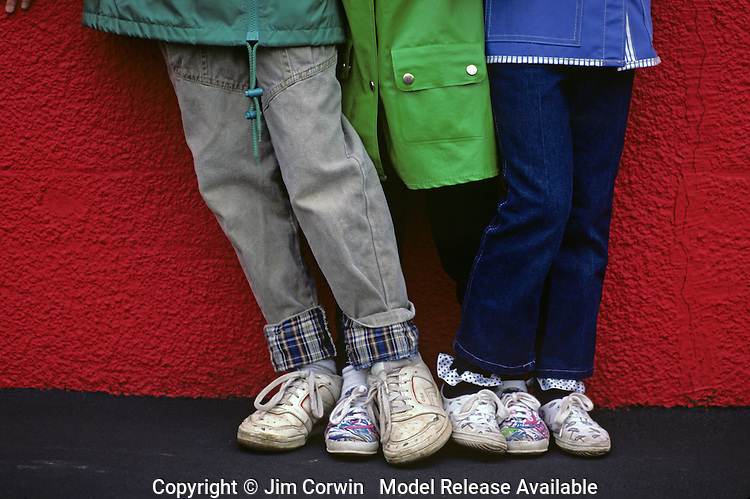 Brother and sisters having fun in front of a red wall close up on tennis shoes Seattle Washington State USA   MR