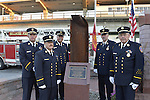 Bellmore, New York, USA. September 11, 2015. L-R, Bellmore Fire Dept. Chief DANIEL HOLL, Pastor and Chaplain JAMES BARNUM, 1st Deputy VINCENT MONTERA, 2nd Deputy TOM STOERGEN, and Chaplain DENNIS RICH stand next to a monument that's a piece of structural steel from the Twin Towers, during the Bellmore Memorial Ceremony for 3 Bellmore volunteer firefighters and 7 residents who died due to 9/11 NYC terrorist attacks. Elevated platform of Bellmore LIRR Station is in background.