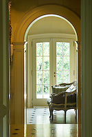 An archway leads to the landing which is furnished with a Louis XV cane-backed sofa