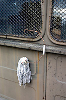 Mop and pail handle hanging on the side of a truck at the site of a mock up of a military mess hall in Poland where soup and bread is served.  Rawa Mazowiecka  Central Poland