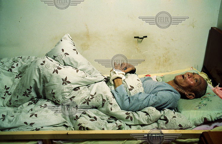An elderly man sleeps in his bed at an old people's home in Shanghai.