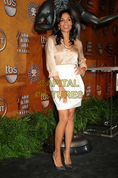 ROSARIO DAWSON .17th Annual Screen Actors Guild Award Nominations held at The Pacific Design Center, West Hollywood, California, USA, 16th December 2010..full length hand on hip white skirt pointy grey gray shoes beige cream silk satin smiling shirt gold cross necklace .CAP/ADM/BP.©Byron Purvis/AdMedia/Capital Pictures.