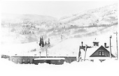 East facing side view of the Rico engine house with the depot to the right and D&amp;RGW box car in the foreground in a winter scene with four feet of snow.<br /> RGS  Rico, CO  Taken by Arend, Lad G. - ca. 1925