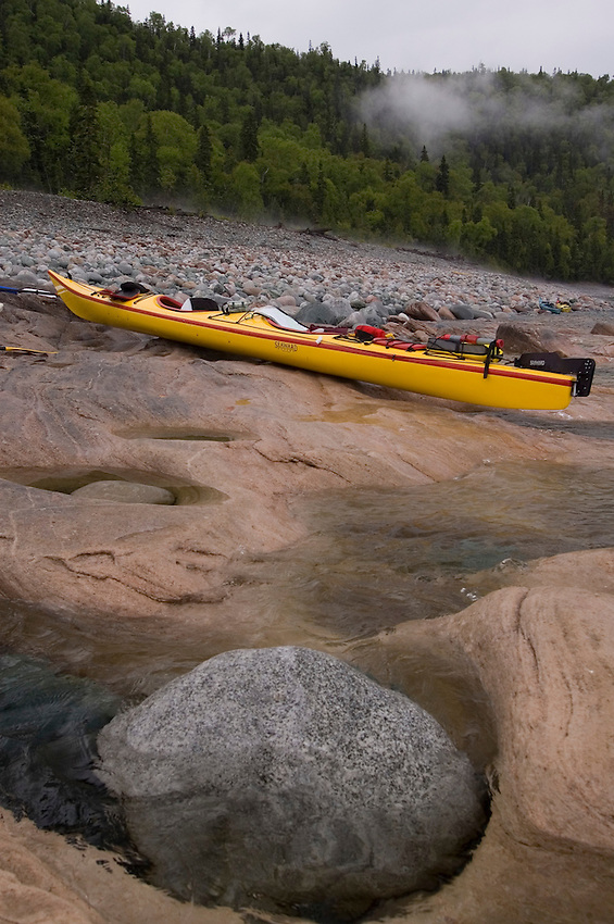 A tandem sea kayak rests on an eroded sandstone beach at Grindstone Point in Lake Superior Provincial Park near Wawa Ontario Canada.