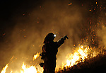 A member of the fire brigade of Belchite works around a fire in Andorra early  on July 23, 2009, near Teruel. Some 500 people were battling on July 22 a wind-fuelled wildfire in northeastern Spain which claimed the lives of four firefighters and seriously injured two others, Defence Minister Carme Chacon said. on July 23, 2009. (C) Pedro ARMESTRE