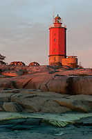 Sun sets on Russarö lighthouse standing guard on a military island outside Hanko, Finland.