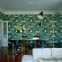 The flamboyant wallpaper in the dining area is a pattern from the Beverley Hills Hotel and the Pace Collection chairs are from Center 44 in New York City
