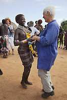 "Ethiopia. Southern Nations, Nationalities, and Peoples' Region. Omo Valley. Turmi. Hamar tribe (also spelled Hamer). Pastoralist group. Marc Vella is a french musician and a nomadic pianist. Over the last 25 years he has travelled with his Grand Piano in around forty countries to celebrate humanity. Creator of ""La Caravane amoureuse"" (The Caravan of Love) he takes people with him to say ""I love you"" to others and ""lovingly conquered"" their hearts and souls. Soizic Triennot (R), Pascale Burger (C back), Brigitte Papeians(C) and Marie-Cecile Tardieu (L), all participants of The Caravane of Love, dance with Hamer women and men to celebrate life and a farewell departure. Hamar women wear an elaborately decorated goatskin, often colored with beads and cowries. Beaded necklaces, bracelets and waistbands adorn their bodies. Hamer women indulge in elaborate hairdressing by decorating their hair with clay and butter twisted into a striking long plait. The Omo Valley, situated in Africa's Great Rift Valley, is home to an estimated 200,000 indigenous peoples who have lived there for millennia. Amongst them are 60'000 to 70'000 Hamar, an Omotic community inhabiting southwestern Ethiopia. They live in Hamer woreda (or district), a fertile part of the Omo River valley, in the Debub Omo Zone of the Southern Nations, Nationalities, and Peoples Region (often abbreviated as SNNPR) which is one of the nine ethnic divisions of Ethiopia. 10.11.15 © 2015 Didier Ruef"