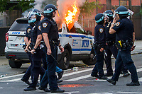 NEW YORK, NEW YORK - MAY 30: View of the police with the car that was on fire during the protest in response to the police officer who killed George Floyd in Brooklyn on May 30, 2020 in New York. The protests spread across the country in at least 30 cities in the United States. United States For the death of unarmed black man George Floyd at the hands of a police officer, this is the latest death in a series of police deaths of black Americans (Photo by Pablo Monsalve / VIEWpress via Getty Images)