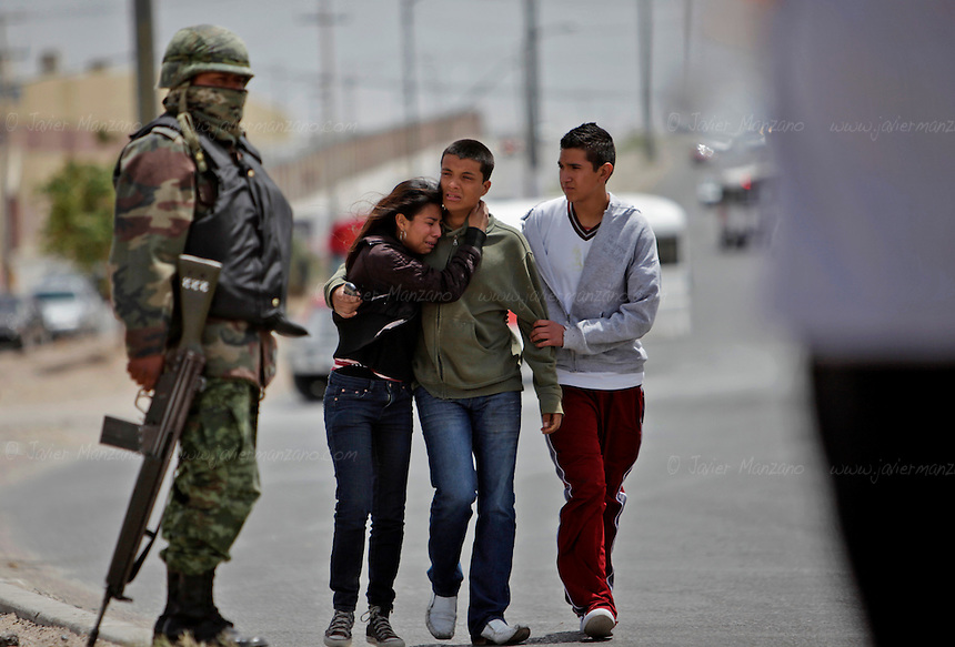 Family members comfort the girlfriend (far left) of 17-year-old Gabriel Arellano Sotelo, the civilian caught in the cross-fire. Sotelo's girlfriend is one month pregnant with Gabriel's child. ..Four Federal Police officers, one female Municipal Police and one civilian were killed outside a gasoline station on the corner of Santiago Troncoso and Durango Ave. in Ciudad Juarez on the afternoon of April 23, 2010. Another woman who was tending to her local business and a Federal Police officer where wounded and transferred to a nearby hospital. According to witnesses, a total of four vans packed with 30 shooters, closed in on the officers with high caliber weapons and opened fire on them around 12:30 pm. .©Javier Manzano
