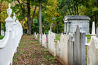 Charming New England picket fence with autumn foliage.