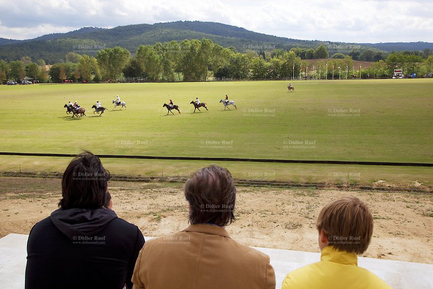 Italy. Tuscany. Polo Club Villa A Sesta is located near the village of Ripaltella and Pietraviva (Arezzo). Riccardo Tattoni (C) is the owner of the Polo Club Villa A Sesta. He is watching a polo game with his son Gualtiero Giori (L) and Nikita Maslov (R). Polo players riding horses and hitting ball during polo game. 17.09.10 © 2010 Didier Ruef