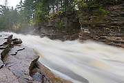 Lower Ammonoosuc Falls in Carroll, New Hampshire on a rainy autumn day. This picturesque waterfall is located on the scenic Ammonoosuc River.