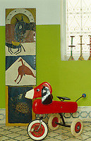 A retro child's tricycle shaped like a dog and a tall wooden painted panel in the hallway
