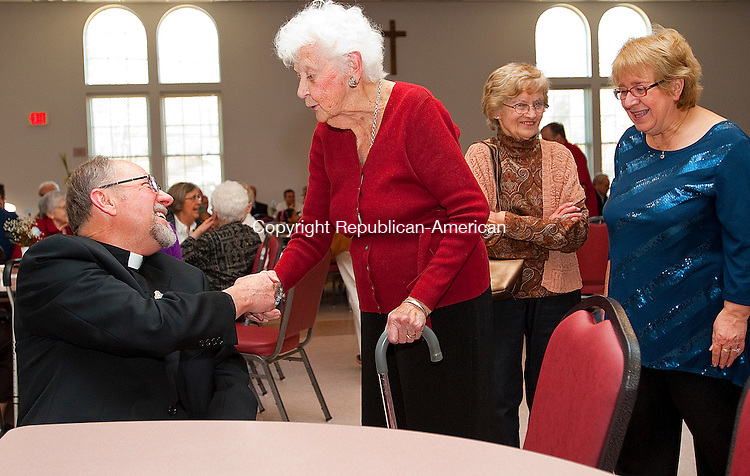 PLYMOUTH. CT, 18 MARCH  2012-031812JS03-Eleanor Phillimore of Plymouth, center, offers well wishes to Father Gerald Dziedic as fellow parishioners, Pat Doherty and Donna Talia, both of Plymouth,  wait to wish him well during a gathering Sunday at The Lyceum in Plymouth. Fr. Dziedic, who was responsible for overseeing the construction of The Lyceum, which has served as a religious and community center for events and helped clean up Main Street and also merged two local churches during his tenure, was recently reassigned to a new parish. .Jim Shannon Republican-American