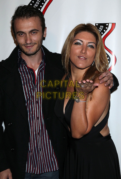 Arber Kucana &amp; Michelle Alexandria <br /> 13th annual Polish film festival at American Cinematheque's Egyptian Theatre, Hollywood, California, USA.<br /> 9th October 2012<br /> half length black suit jacket dress blue stripe shirt red hand arm blowing kiss stubble facial hair <br /> CAP/ADM/RE<br /> &copy;Russ Elliot/AdMedia/Capital Pictures