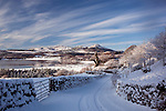Scenic winter landscape snow covered road winding past Almorness House looking across Orchardton Bay to Bengairn and Screel Hill Galloway Scotland UK