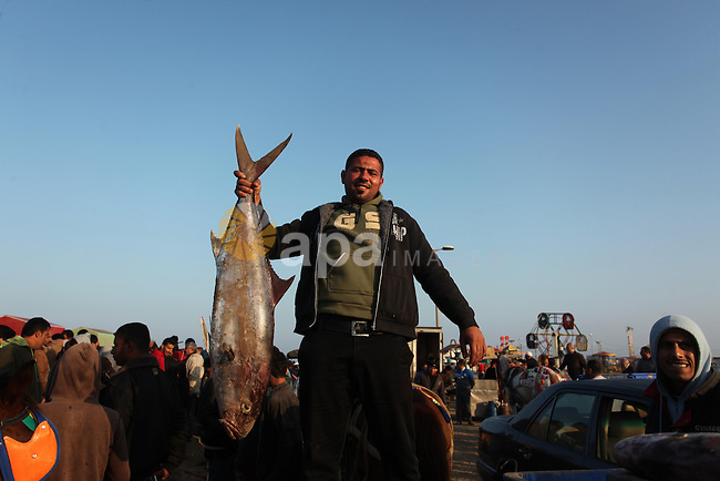 A Palestinian fisherman displays fish for sale, in Gaza seaport, on April 4, 2016. Israel on Sunday extended the distance it permits Gaza fishermen to head out to sea along certain parts of the coastline of the enclave, which is run by the Islamist group Hamas. The fishing zone was expanded from six nautical miles (11 km) to nine (16 km) along Gaza's central and southern shores, a step that Israeli authorities said should result in a bigger catch in deeper waters, where fish are more abundant. Photo by Ashraf Amra