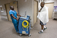 mayoheart 158497-- Charles Okeke walks with JoJo Okyere in the Mayo Clinic Hospital. Anytime Okeke needs to go somewhere, he must be accompanied by a technician to monitor his Total Artificial Heart. The Total Artificial Heart weighs 400 pounds keeping him stuck in the hospital until he can get a heart transplant or until he can be hooked up to a more portable version. (Pat Shannahan/ The Arizona Republic)