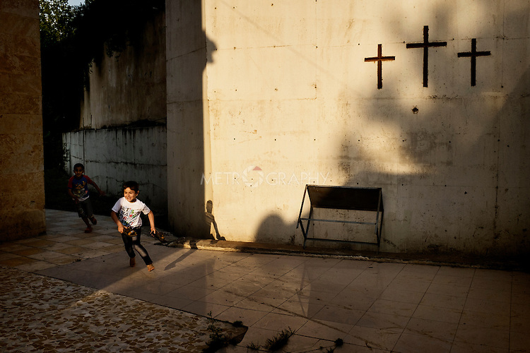 20/05/15. Shaqlawa, Iraq. -- A displaced Christian boy from Qaraqosh inside the courtyard at Al Shuhada church. Around 800 Christian families have arrived to Shaqlawa since August 2014. Most of them have now been moved to shipping containers in a new camp in Erbil.