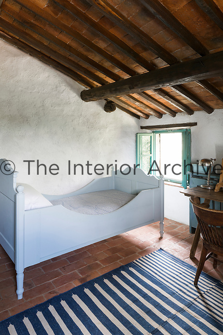 A child's bedroom has a rustic simplicity. Traditional local materials were kept during the restoration of the house, such as the terracotta tiles on the floor and ceilings and the original massive wooden beams.