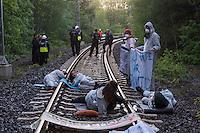 """Klimacamp """"Ende Gelaende"""" bei Elsterheide in der brandenburgischen Lausitz.<br /> Mehrere tausend Klimaaktivisten  aus Europa wollen zwischen dem 13. Mai und dem 16. Mai 2016 mit Aktionen den Braunkohletagebau blockieren um gegen die Nutzung fossiler Energie zu protestieren.<br /> Im Bild: Polizeibeamte beobachten Klimaaktivsten aus Schweden, Oesterreich, Finnland, und Deutschland die sich auf den Schienen einer Kohletransportstrecke angekettet haben um sie zu blockieren.<br /> 13.5.2016, Elsterheide/Brandenburg<br /> Copyright: Christian-Ditsch.de<br /> [Inhaltsveraendernde Manipulation des Fotos nur nach ausdruecklicher Genehmigung des Fotografen. Vereinbarungen ueber Abtretung von Persoenlichkeitsrechten/Model Release der abgebildeten Person/Personen liegen nicht vor. NO MODEL RELEASE! Nur fuer Redaktionelle Zwecke. Don't publish without copyright Christian-Ditsch.de, Veroeffentlichung nur mit Fotografennennung, sowie gegen Honorar, MwSt. und Beleg. Konto: I N G - D i B a, IBAN DE58500105175400192269, BIC INGDDEFFXXX, Kontakt: post@christian-ditsch.de<br /> Bei der Bearbeitung der Dateiinformationen darf die Urheberkennzeichnung in den EXIF- und  IPTC-Daten nicht entfernt werden, diese sind in digitalen Medien nach §95c UrhG rechtlich geschuetzt. Der Urhebervermerk wird gemaess §13 UrhG verlangt.]"""