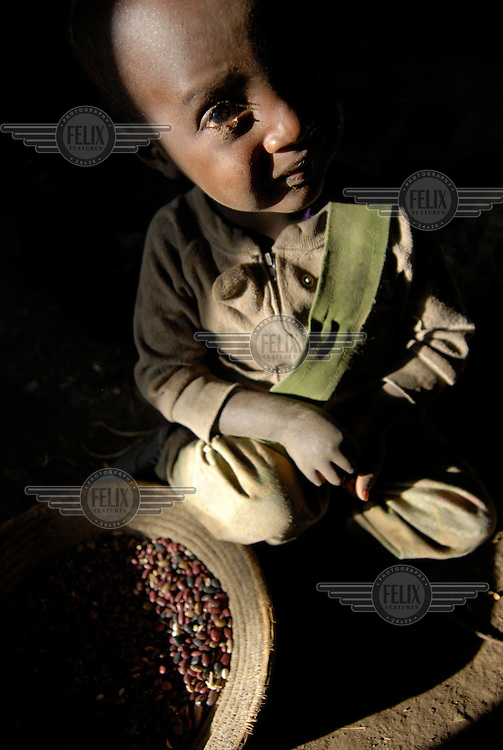 A child helps his mother sort grain.
