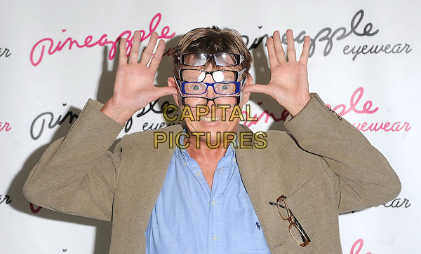 KEVIN KENNEDY.Photocall to launch the Pineapple Studios Eyewear range at Pineapple Studios, Covent Garden, London, England..August 4th 2010 .half length shirt jacket suit palms hands  glasses wearing funny blue brown.CAP/BEL.©Tom Belcher/Capital Pictures.