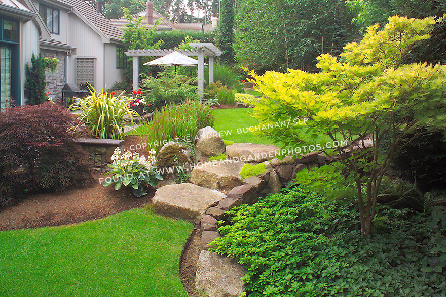 "Even the large stone stairs seem to ""spill"" from an upper lawn to a lower one, as water would spill between ponds, in this scene from the upper, walking garden in this otherwise small suburban backyard east of Seattle.  Imagine the boulders as pondside platforms and the Japanese Bloodgrass as cattails in this Zen-like interpretation of a traditional Japanese rock garden. Design by Sander Groves landscapes, Inc."