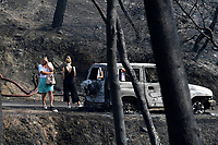 Pictured: Two women stand in disbelief in the aftermath of the wild forest fires in the Neos Voutzas area near Rafina, Greece. Tuesday 24 July 2018<br /> Re: Deaths caused by wild forest fires throughout Greece.