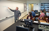 """Classroom photos from General Physics II Laboratory in the Hammetman Science Center room 108 with Igor Umanskiy, Non-Tenure Track Assistant Professor, Physics. April 12, 2018.<br /> <br /> The lab is simply called """"Lenses"""". The students investigate how to determine the focal length of a converging lens. The apparatus is called an """"Optical Bench"""" and consists of an incandescent light source along with a lens, an imaging target and a screen upon which to focus the image. By projecting the target through the lens onto the screen at varying distances the focal length of the lens can be determined.<br /> <br /> (Photo by Marc Campos, Occidental College Photographer)"""